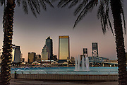 City skyline and Friendship Fountain from the Southbank Riverwalk along the St. John's River at sunset in Jacksonville, Florida.
