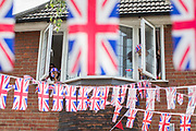 UNITED KINGDOM, London: 08 May 2020 <br /> Charlie Fenner, aged 6 (left) and her father James Fenner (right) lean out of their windows of their decorated house in South West London this afternoon in celebration of the 75th anniversary of Victory in Europe Day (VE Day). It celebrates when Winston Churchill announced Nazi Germany's unconditional surrender of it's armed forces marking the end of Work War II in Europe.