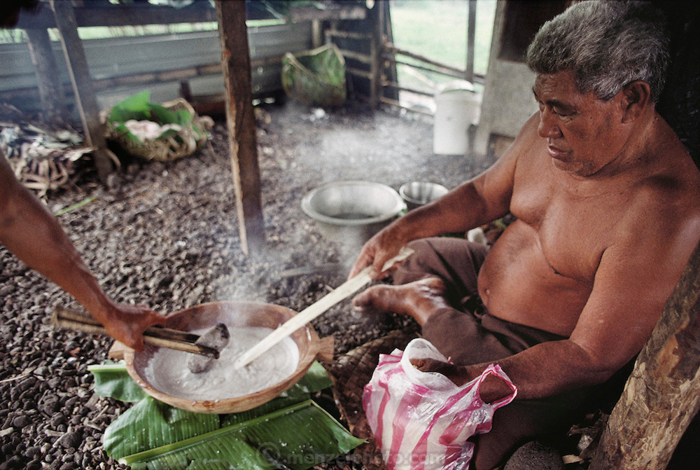 Auseuga Lagavale, the matai (head) of his extended family, is cooking his favorite coconut sauce, in preparation for a feast at the Lagavale home in Western Samoa. The recipe: wring out fresh coconut meat with the fibers from the husk, boil juice in a bowl by droping in rocks heated by fire, dribble in sugar, stir constantly until the milky white sauce thickens. Work, Food. {{He is cooking in the family's detached cooking shed behind the main house. The Lagavale family lives in a 720-square-foot tin-roofed open-air house with a detached cookhouse in Poutasi Village, Western Samoa. Material World Project.