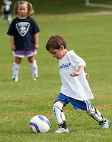 Elijah Nadeau from Team Metrocast dribbles the ball downfield during the Laconia Youth Soccer programs opening day game against Laconia Police Team at Opechee Park Saturday morning.  (Karen Bobotas/for the Laconia Daily Sun)