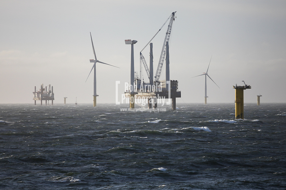 19/03/2014. Gwnt y Mor Wind Farm, North Wales, UK. A view of the installation jack-up barges, Sea Jack (right) and Friedrich Ernestine (left), on the Gwynt y Mor Offshore Wind Farm installing a wind turbine. Photo credit : Rob Arnold