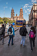Young students walk through the Plaza De Armas toward the Cathedral of San Luis Potosi in the historic center of the state capital of San Luis Potosi, Mexico. Also known as the San Luis Potosi Metropolitan Cathedral, it is consider the most important monument in the state and the first Baroque style building constructed in 1670 on the site of a parish church first built in 1593.