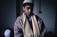United Kingdom. Birmingham. Birmingham:  In spite of this Orthodox Islamic education, the children are not unaware of the occidental society.  This boy in prayer wears a coca-cola badge.  Birmingham  United Kingdom     /  Birmingham: malgré cet enseignement islamique orthodoxe, les enfants ne sont pas insensibles à la société occidentale. Ce garçon en prière arbore un badge Coca Cola. Coventry islamic boy school .  Birmingham  Grande Bretagne   /  R00017/    L0007462  /  R00017  /  P0005560