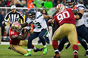 San Francisco 49ers defensive end Tank Carradine (95) slips off Seattle Seahawks quarterback Russell Wilson (3) at Levi's Stadium in Santa Clara, Calif., on November 26, 2017. (Stan Olszewski/Special to S.F. Examiner)