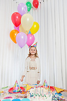 Portrait of a happy girl holding party balloons with cake on table