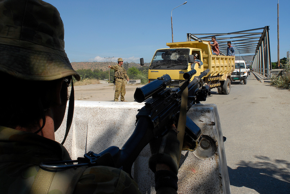 Australian Peacekeeprs man a roadblock at the Bridge in Comora. Australian soldiers search suspected gang members for weapons near the Comora area of Dili, a hot point for clashes between rival gangs, the ( Lorosae) and the Westerners (Loromonu). Much of the violence is tat for tat revenge for the lotting and burning of homes. 05/06/06 East Timor