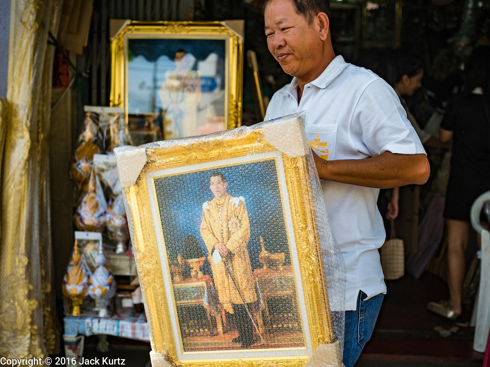 01 DECEMBER 2016 - BANGKOK, THAILAND: A man buys a portrait of HRH Crown Prince Maha Vajiralongkorn, who will soon be the new King of Thailand. Thailand's parliamentary body, the National Legislative Assembly, invited HRH Crown Prince Maha Vajiralongkorn to be king following the death of the Crown Prince's father, Bhumibol Adulyadej, the Late King of Thailand. The invitation marked the formal beginning of the process of naming the new King, although Crown Prince Vajiralongkorn was the heir apparent and Bhumibol's appointed successor. Shops that sell royal paraphernalia are now selling new portraits of  Crown Prince Vajiralongkorn which will be displayed alongside portraits of his late father. King Bhumipol died on Oct 13.      PHOTO BY JACK KURTZ