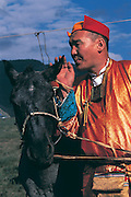 Monk blessing race horse<br /> Naadam horse race<br /> Jockey's aged 4-12 years and most often girls<br /> Ulaanbaatar race track<br /> Mongolia