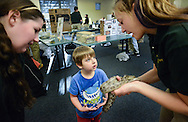 Lindsey Schick (L) looks on as Sarah Cvach (R) holds a corn snake as Vincent Fernandez (C) pets it during an event in which Delaware Valley College students will host a family friendly Animals in the Public Eye Monday March 23, 2015 at the Doylestown Free Library in Doylestown, Pennsylvania. (Photo by William Thomas Cain/Cain Images)
