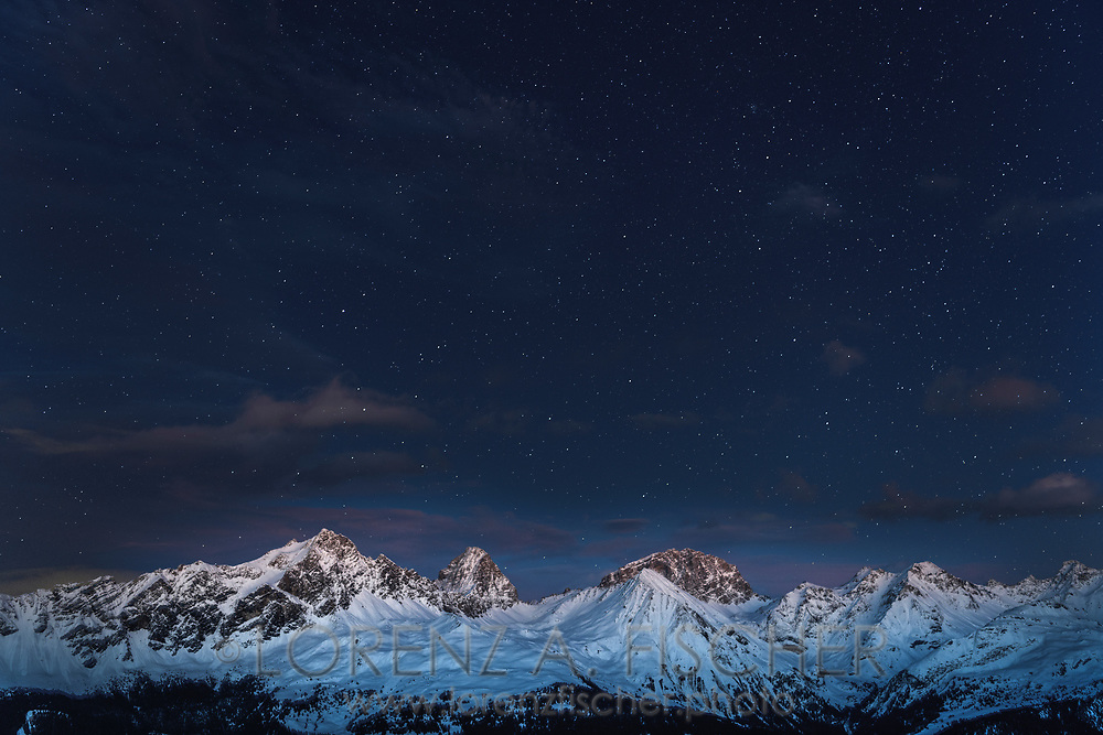 Night sky with stars over the group of the Bergüner Stöcke with the peaks Piz Mitgel, Corn da Tinizong and Piz Ela at late dusk, Parc Ela, Grisons, Switzerland