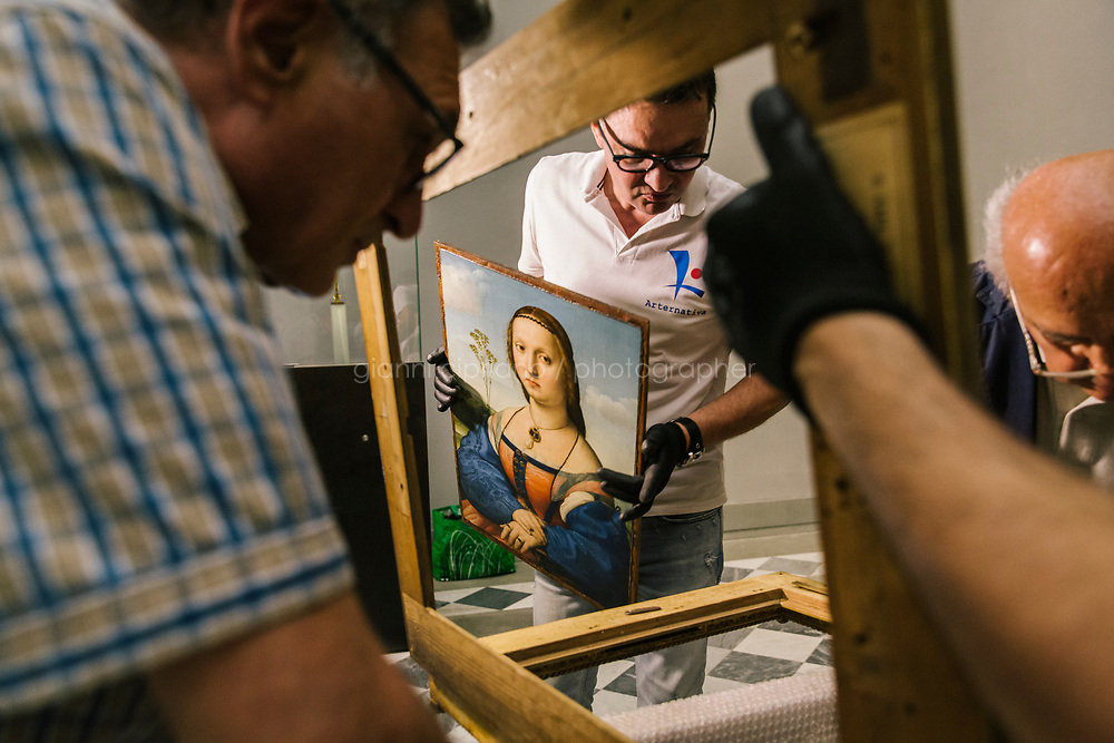 FLORENCE, ITALY - 3 JUNE 2018: Technicians are seen here at work as they position the dual portraits of Agnolo Doni and his wife Maddalena Strozzi, painted by Raphael, in room 41at the Uffizi, in Florence, Italy, on June 3rd 2018.<br /> <br /> As of Monday June 4th 2018, Room 41 or the &ldquo;Raphael and Michelangelo room&rdquo; of the Uffizi is part of the rearrangement of the museum's collection that has<br /> been defining Uffizi Director Eike Schmidt&rsquo;s grander vision for the Florentine museum.<br /> Next month, the museum&rsquo;s Leonardo three paintings will be installed in a<br /> nearby room. Together, these artists capture &ldquo;a magic moment in the<br /> first decade of the 16th century when Florence was the cultural and<br /> artistic center of the world,&rdquo; Mr. Schmidt said. Room 41 hosts, among other paintings, the dual portraits of Agnolo Doni and his wife Maddalena Strozzi painted by Raphael round 1504-1505, and the &ldquo;Holy Family&rdquo;, that Michelangelo painted for the Doni couple a year later, known as the<br /> Doni Tondo.