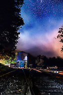 An atmospheric fog pours over a water tower, enclosing the starry skies near the old railroad tracks in Cass, West Virginia.