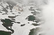Snow patches with meltwater channels in the fog, Säntis, Alpstein, Switzerland
