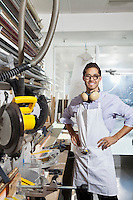 Portrait of a skilled worker standing with hands on hips in workshop