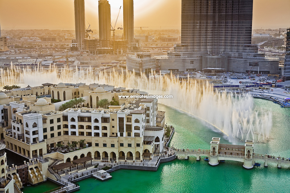 Dubai Fountain in the Downtown area. The building in the foreground is Souk Al Bahar, while in the background, Burj Khalifa is still being completed.