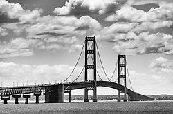 "The Mackinac Bridge, the longest suspension bridge in the Western Hemisphere, connects Michigan's lower and upper peninsulas. The Mackinac Bridge, including approaches is roughly file miles long with the roadbed at mid-span approximately 200 feet above the Straits of Mackinac where Lake Michigan and Lake Huron meet. As it is a suspension bridge, the bridge roadbed can slowly shift as much as 35 feet during severe winds. The Mackinac Bridge carries Interstate 75 (I-75). The bridge, also known as the ""Mighty Mac"" or ""Big Mac"" was opened in 1957. Pedestrians are not allowed to walk across the bridge except during the Mackinac Bridge Walk which is held every Labor Day. This view of the bridge is from Bridge View Park in Saint Ignace."