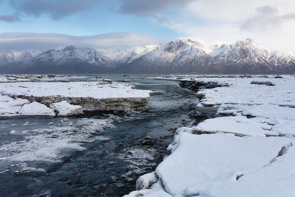 Reurrection Creek meanders through ice and silt at low tide at Hope in Southcentral Alaska. Winter. Morning.