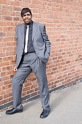 Young man wearing suit leaning against a wall,
