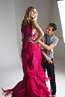 Male designer adjusting dress on fashion model in studio