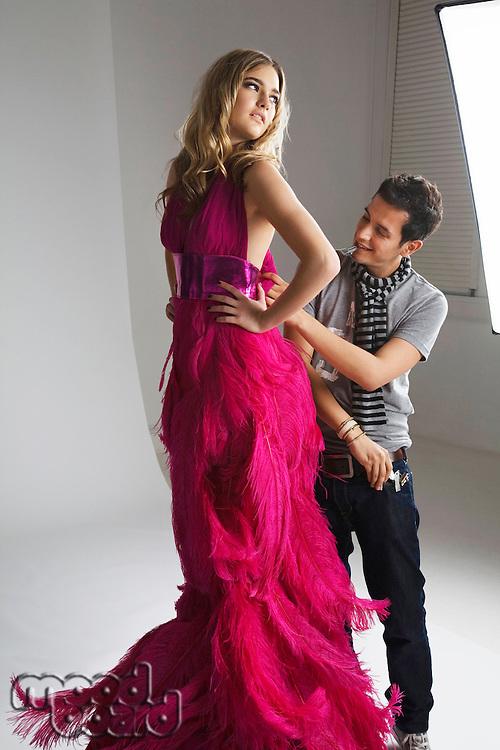 Male designer adjusting dress on fashion model in studio