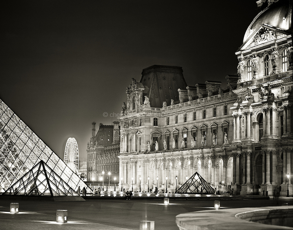 La Grande Roue peeks between the iconic modern sculputre of the Louvre and its original historic museum.