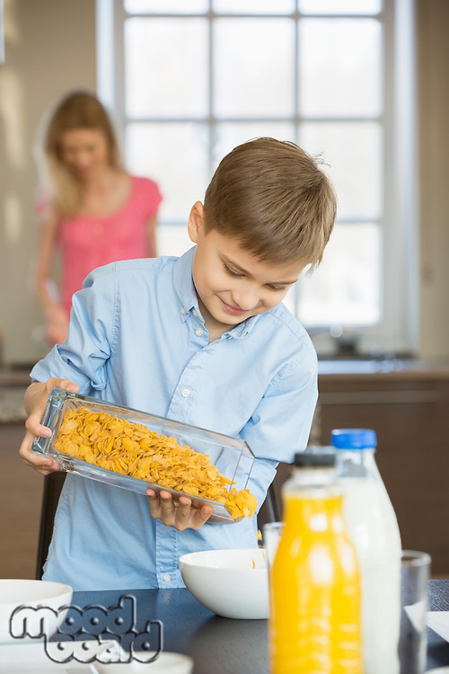 Boy pouring corn flakes in bowl with mother standing in background