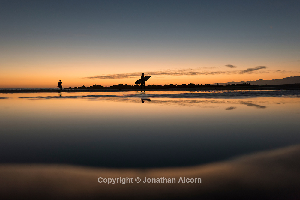 A surfer walks in during low tide at Venice