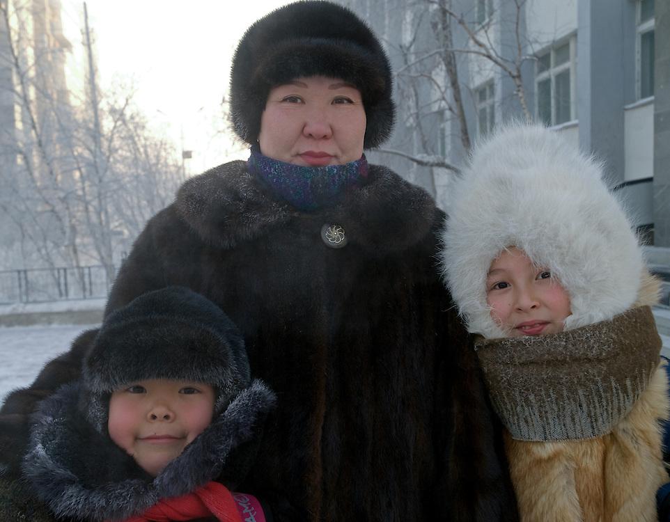 Jakutische Mutter und ihre Kinder mit Kopfbedeckung gesch&uuml;tzt gegen die extreme Kaelte in der Innenstadt von Jakutsk. Jakutsk wurde 1632 gegruendet und feierte 2007 sein 375 jaehriges Bestehen. Jakutsk ist im Winter eine der kaeltesten Grossstaedte weltweit mit durchschnittlichen Winter Temperaturen von -40.9 Grad Celsius. Die Stadt ist nicht weit entfernt von Oimjakon, dem Kaeltepol der bewohnten Gebiete der Erde.<br /> <br /> Yakut mother and her children protected with headgears against the extrem climate  in the city center of Yakutsk. Yakutsk was founded in 1632 and celebrated 2007 the 375th anniversary - billboard announcing the celebration. Yakutsk is a city in the Russian Far East, located about 4 degrees (450 km) below the Arctic Circle. It is the capital of the Sakha (Yakutia) Republic (formerly the Yakut Autonomous Soviet Socialist Republic), Russia and a major port on the Lena River. Yakutsk is one of the coldest cities on earth, with winter temperatures averaging -40.9 degrees Celsius.