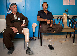 © Licensed to London News Pictures. 03/04/2013. London, UK. UN International Mine Awareness Day [FILE PHOTO NOT FOR ONLINE USE]. Two male mine-strike victims sit on chairs as they take a break from walking and testing their new prosthetic legs at the Kurdish Organisation for the Rehabilitation of the Disabled (KORD) centre in Sulimaniyah.  Photo credit: Matt Cetti-Roberts/LNP