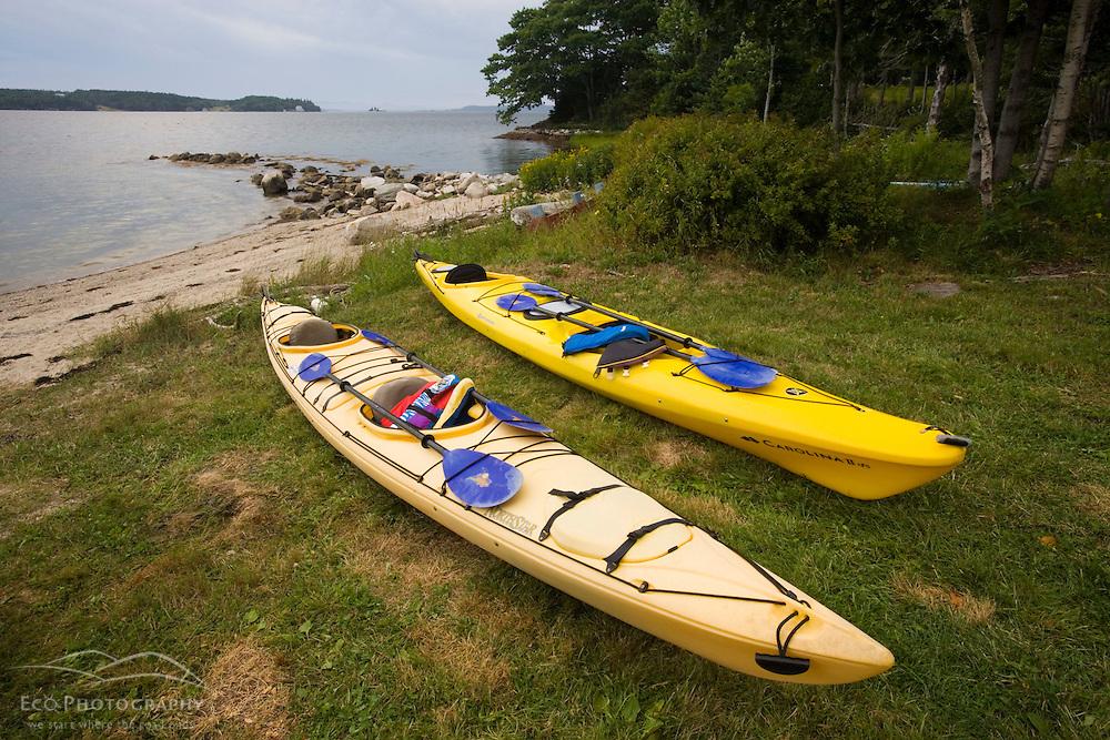 Sea kayaks on the shoreline og Eggemoggin Reach at the Oakland House Seaside Resort in Brooksville, Maine.  Blue Hill Peninsula.  East Penobscot Bay.