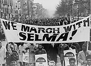 Marchers carrying banner lead the way as 15,000 parade. Photograph shows marchers carrying banner 'We march with Selma!' on street in Harlem, New York City, New York. 1965 March. ' World Telegram & Sun' photograph by Stanley Wolfson.