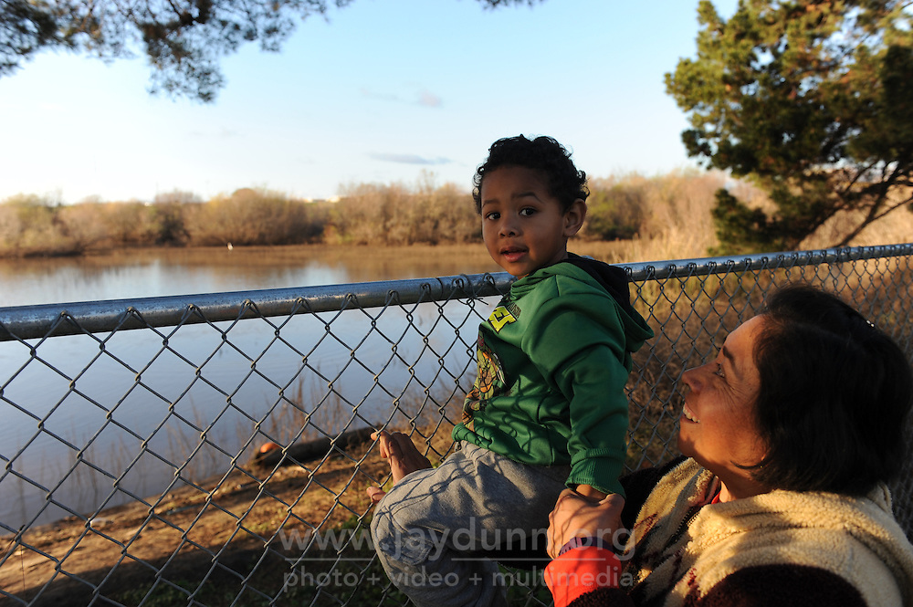 A mom gives her child a boost in front of Carr Lake on Tuesday, February 2nd, 2016 at the nearly-completed Acosta Plaza Recreation Area in east Salinas, CA.