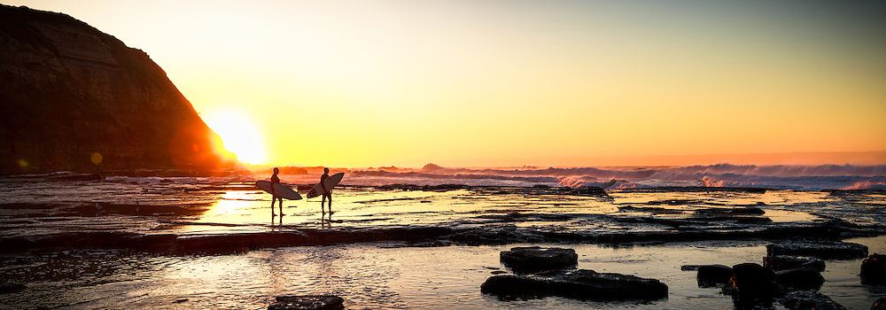 Surfers watching surf at Dawn, Susan Gilmore Beach, Newcastle, Australia. For Visit Newcastle