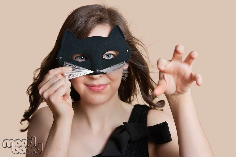 Portrait of a young woman looking through eye mask imitating as cat over colored background
