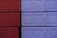 "Close up of burgundy and periwinkle blue bars of lavender soap stacked on one another. French lettering embossed on each bar translates to English as ""a bit of Provence"""