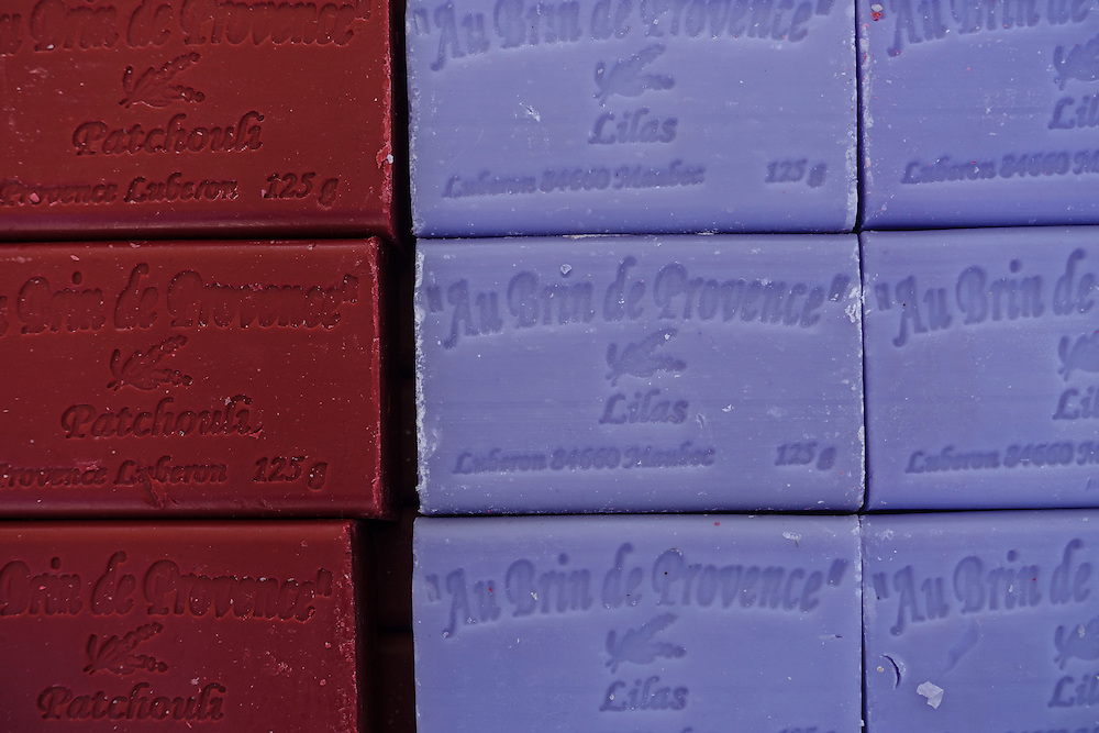 """Close up of burgundy and periwinkle blue bars of lavender soap stacked on one another. French lettering embossed on each bar translates to English as """"a bit of Provence"""""""