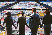 Volunteers pause for a moment of silence after spreading the entire AIDS Memorial Quilt out along the National Mall October 11, 1996 in Washington, DC.
