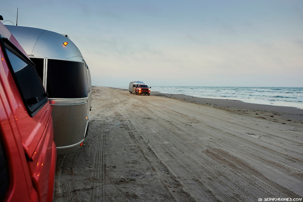 Recreational vehicles (RVs) drive along the beach on the Padre Island National Seashore of Texas.