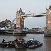 London's Tower Bridge in the early evening, with barges on the River Thames in the foreground. Constructed in the late 1800s, the ornate Tower Bridge is one of London's iconic landmarks. It gets its name from the nearby Tower of London on the northern bank of the River Thames.