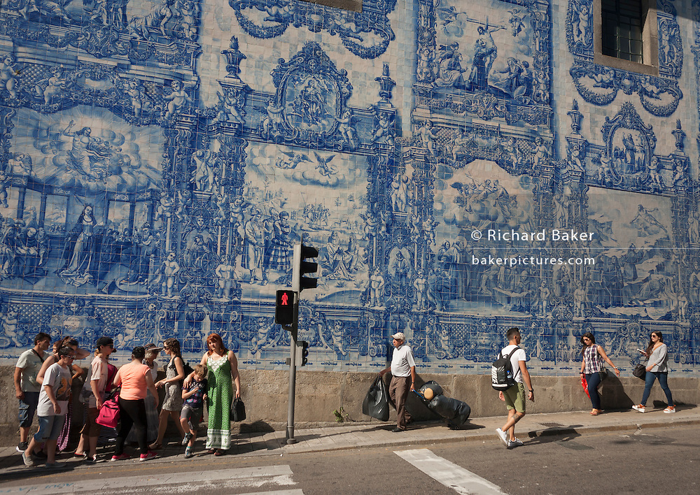 Portuguese citzens walk along the Rua de Fernandes Tomas where Azulejo tiles on the exterior of Capela Das Almas are seen above, on 19th July, in Porto, Portugal. The Church's magnificent panels depict scenes from the lives of various saints, including the death of St Francis and the martyrdom of St Catherine. Eduardo Leite painted the tiles in a classic 18th-century style, though they actually date back only to the early 20th century. (Photo by Richard Baker / In Pictures via Getty Images)