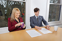 Cheerful young businesspeople with coffee mugs and documents at conference table