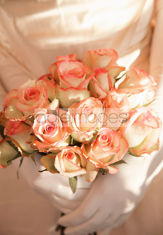 Close up of a bride gloved hands holding a bouquet of roses