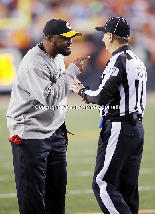 Pittsburgh Steelers head coach Mike Tomlin points as he gives an earful to line judge Ron Marinucci (107) during the NFL AFC Wild Card playoff football game against the Cincinnati Bengals on Saturday, Jan. 9, 2016 in Cincinnati. The Steelers won the game 18-16. (©Paul Anthony Spinelli)