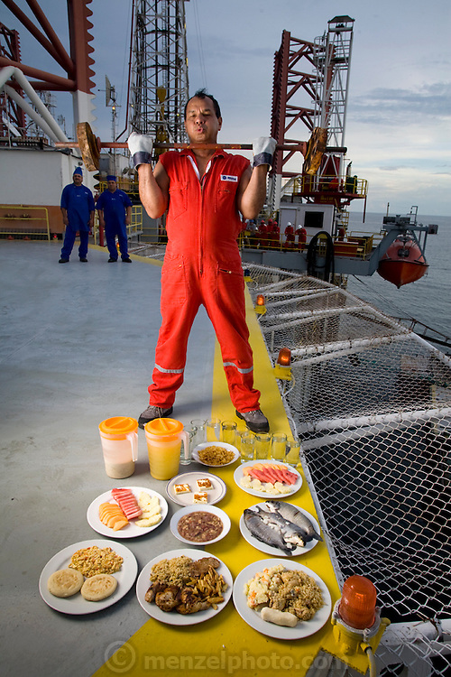 "Oswaldo Gutierrez, Chief of the PDVSA Oil Platform GP 19 in Lake Maracaibo, Venezuela with his typical day's worth of food. (From the book What I Eat: Around the World in 80 Diets.) The caloric value of his day's worth of food on a day in December was 6000 kcals. He is 52; 5'7"" and 220 pounds. Gutierrez works on the platform for seven days then is off at home for seven days.   While on the platform he jogs on its helipad, practices karate, lifts weights, and jumps rope to keep fit. His food for the seven days comes from the platform cafeteria which, though plagued with cockroaches, turns out food choices that run from healthful to greasy-fried. Fresh squeezed orange juice is on the menu as well and Gutierrez drinks three liters of it a day himself. His diet changed about ten years ago when he decided that he'd rather be more fit than fat like many of his platform colleagues. PDVSA is the state oil company of Venezuela. MODEL RELEASED."