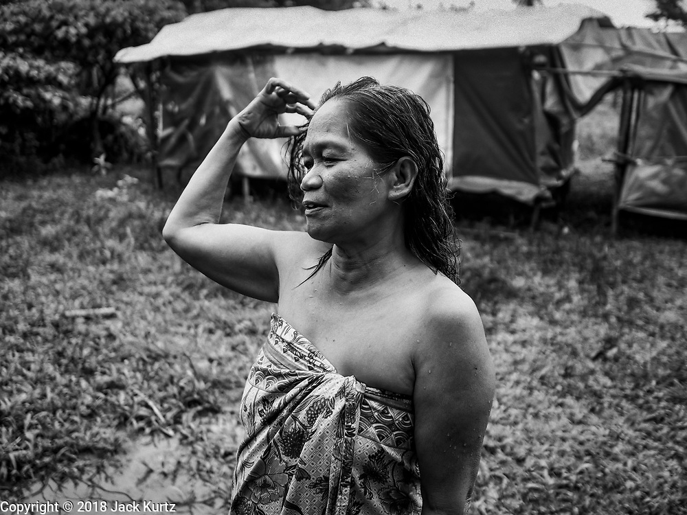 26 JANUARY 2018 - SANTO DOMINGO, ALBAY, PHILIPPINES: A woman who was evacuated from the Mayon volcano washes her hair near the tent she's living in in a field near Santo Domingo. Mayon Volcano was relatively quiet Friday, but the number of evacuees swelled to nearly 80,000 as people left the side of  the volcano in search of safety. There are nearly 12,000 evacuees in Santo Domingo, one of the most impacted communities on the volcano. The number of evacuees is impacting the availability of shelter space. Many people in Santo Domingo, on the north side of the volcano, are sleeping in huts made from bamboo and plastic sheeting. The Philippines is now preparing to house the volcano evacuees for up to three months.        PHOTO BY JACK KURTZ