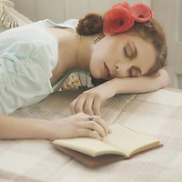 Girl with flowers in her hair sleeping with an open book