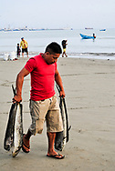 A merchant with four fresh fishes in his hands.  Port of Manta.  Ecuador