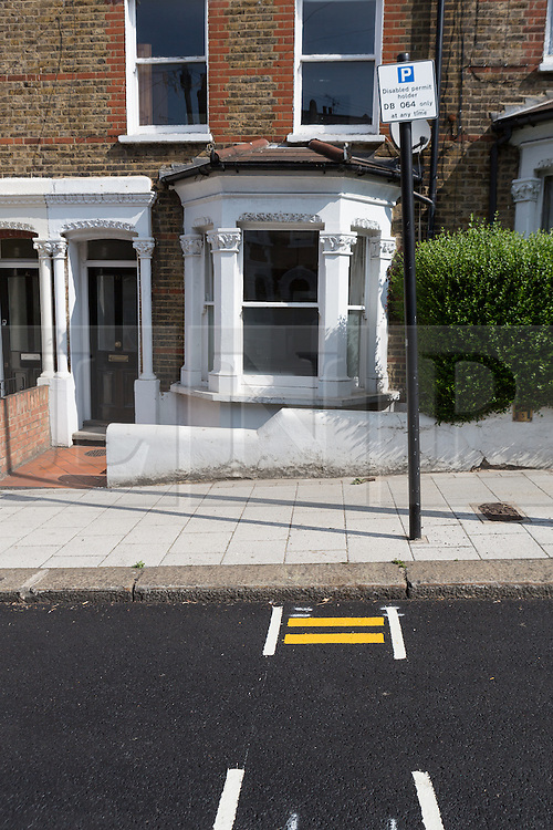 """© Licensed to London News Pictures. 09/07/2015. London, UK. Freshly painted minature double yellow lines in Mossbury Road, Clapham Junction. The tiny double yellow lines, measure approximately one foot in length and were repainted after Wandsworth Council resurfaced the road. There are two identical sets either side of a disabled parking bay. Owner of one of the properties behind the new road markings, Steven Taylor (not pictured) says """"They're so funny, what on earth could you park in there? They're not even big enough for a bike."""" Photo credit : Vickie Flores/LNP"""