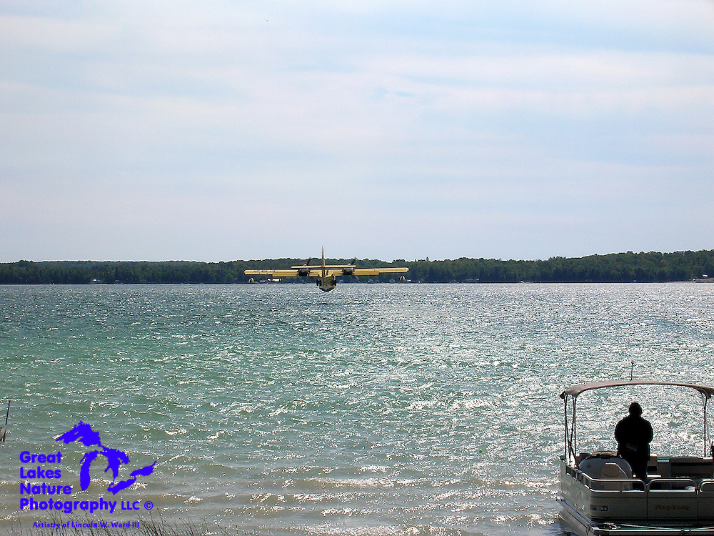 In this 2007 shot, my wife watches as a water bomber aircraft has just flown over our cabin, and is about to lightly touch down on the surface of North Manistique Lake. The pilot repeated this operation to reload his water tanks and return to the Sleeper Lake Forest Fire at 15 minute intervals. This provided our kids and guests a fascinating bit of entertainment that they hadn't expected.