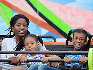 From left, Johanne Mew, Sehra Mew and Zion Mew, all of Morrisville, Pennsylvania enjoy a ride during the Southampton Days Carnival as part of their July 4th celebration Saturday July 4, 2015 in Upper Southampton, Pennsylvania. (Photo by William Thomas Cain)
